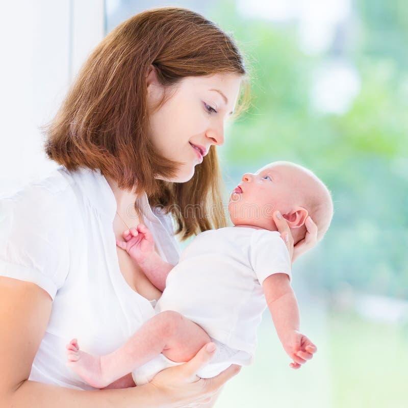 Junge Mutter und ihr neugeborenes Baby am großen Fenster lizenzfreies stockfoto