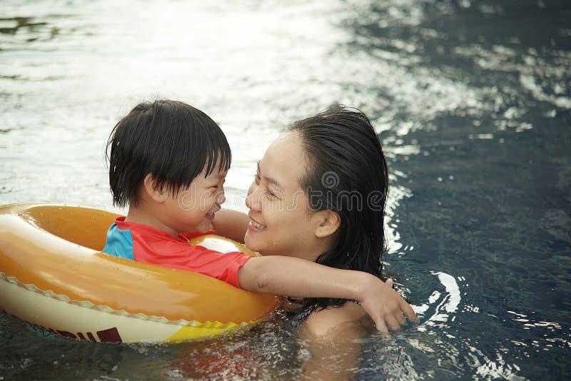 Junge Mutter und ihr Sohn, die den Spaß zusammen spielt am Swimmingpool hat stockfotografie