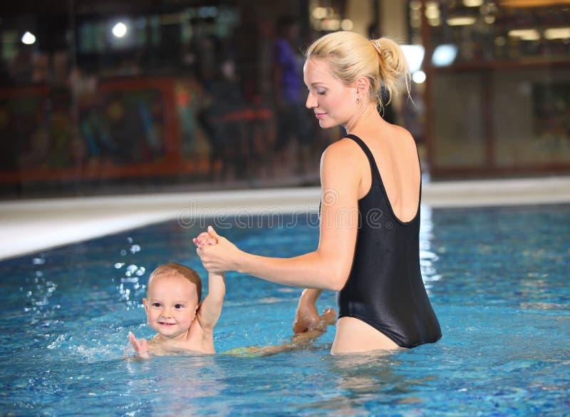 Junge Mutter und ihr Sohn in einem Swimmingpool lizenzfreie stockbilder