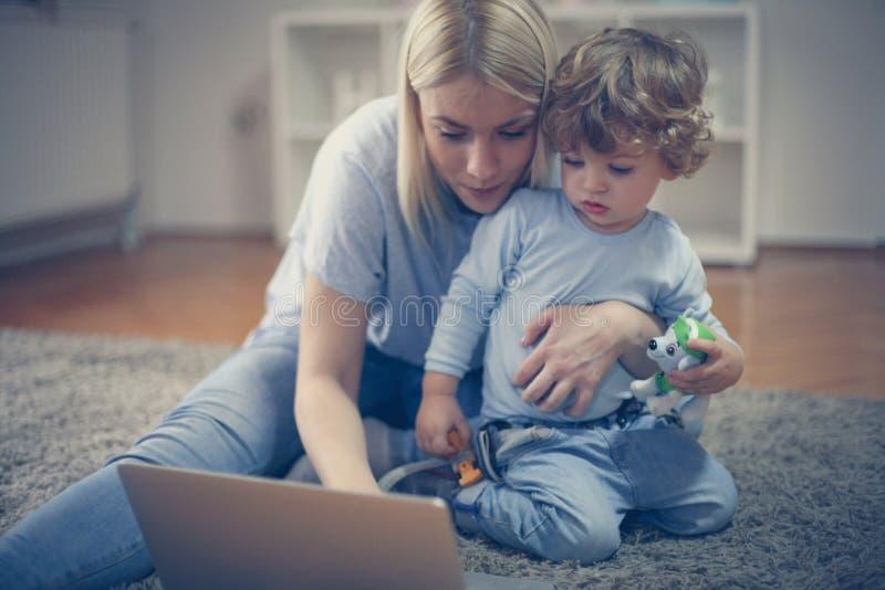 Junge Mutter und ihre aufpassenden Karikaturen des Babys online lizenzfreies stockbild