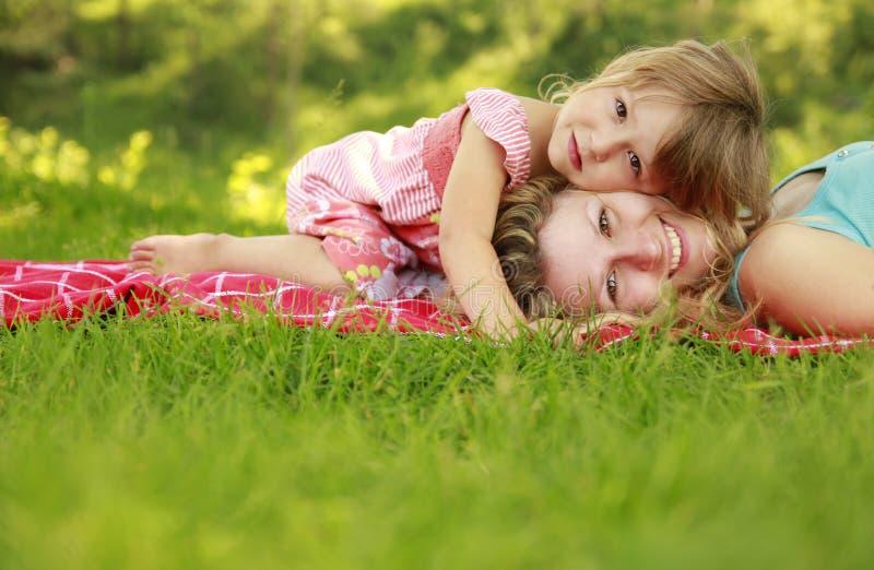 Junge Mutter und ihre kleine Tochter, die auf Gras spielt lizenzfreies stockfoto