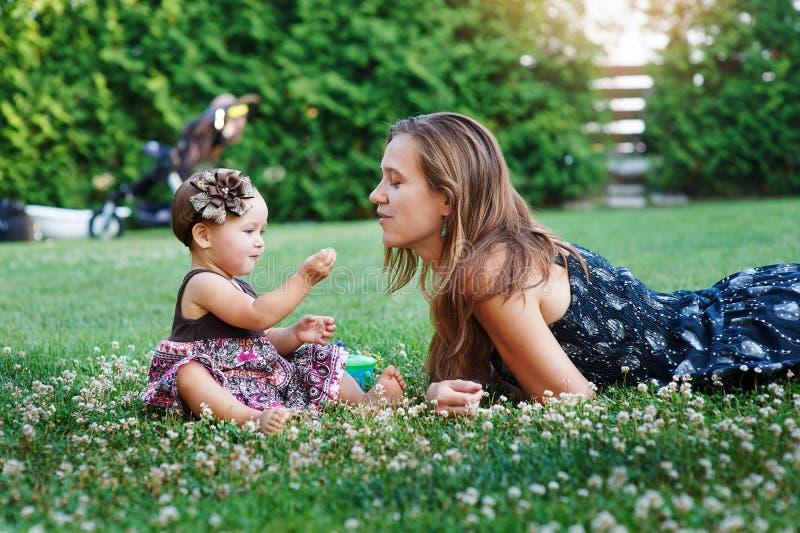 Junge Mutter und ihre kleine Tochter, die auf Gras spielt lizenzfreie stockfotografie