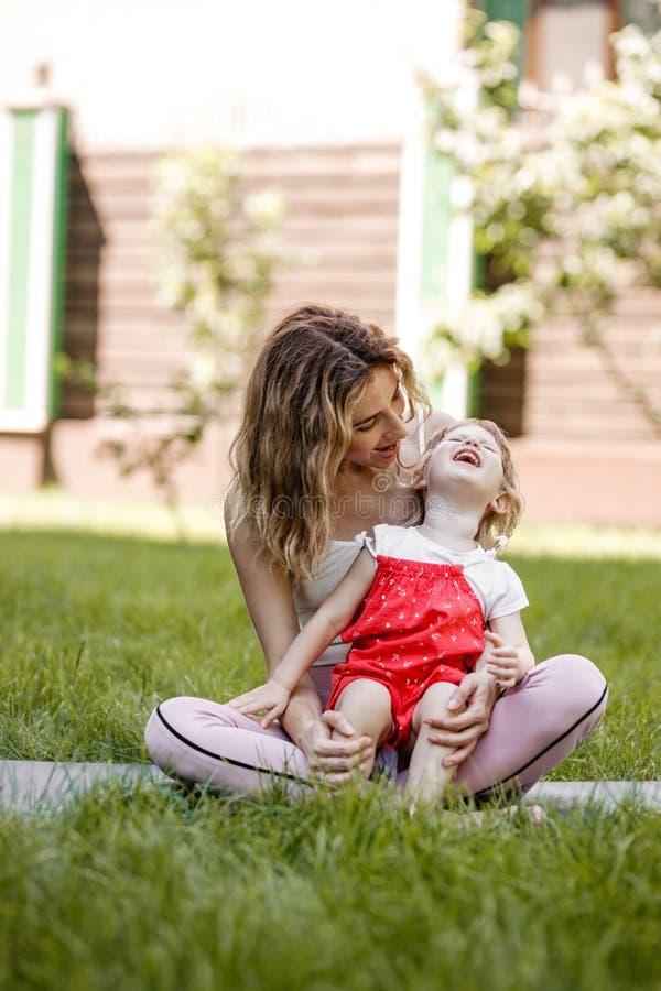 Junge Mutter und ihre kleine Tochter haben den Spaß, der auf dem Rasen im Garten an einem warmen Sommertag sitzt lizenzfreies stockfoto