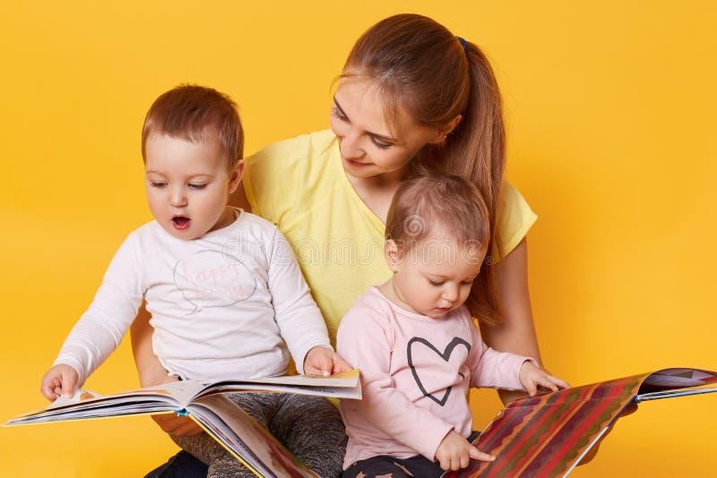 Junge Mutter und ihre kleinen Babytochterlesebücher, Blick auf den bunten Seiten, momny hält Kinder in ihren Knien während stockbilder