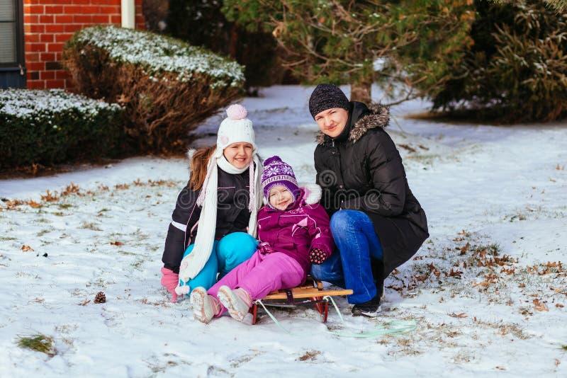 Junge Mutter und ihre Töchter, die Spaß am Wintertag haben stockbild