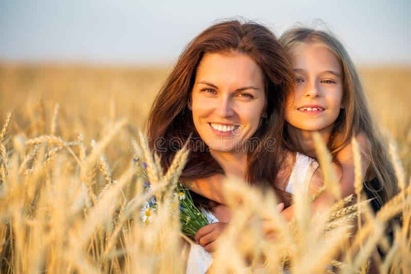Junge Mutter und ihre Tochter auf goldenem Weizenfeld bei Sonnenuntergang lizenzfreie stockbilder