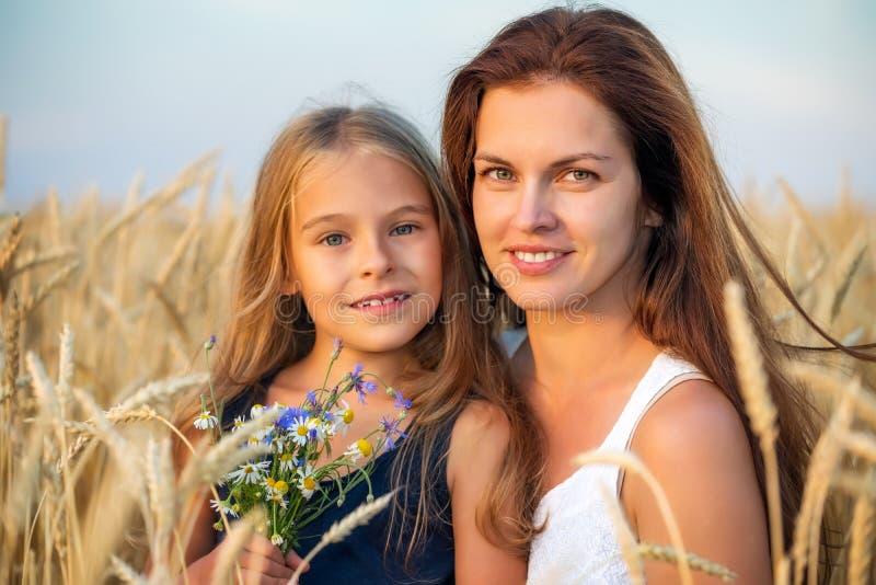 Junge Mutter und ihre Tochter auf goldenem Weizenfeld bei Sonnenuntergang lizenzfreie stockfotos