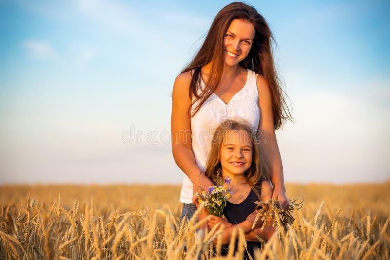 Junge Mutter und ihre Tochterstellung auf Weizenfeld bei Sonnenuntergang lizenzfreies stockbild