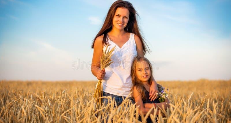 Junge Mutter und ihre Tochterstellung auf Weizenfeld bei Sonnenuntergang stockfotos