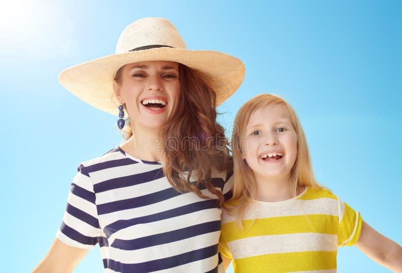 Junge Mutter und Kind gegen blauen Himmel lizenzfreie stockbilder