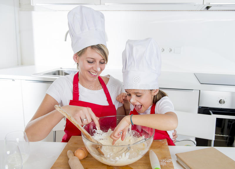Junge Mutter und kleine süße Tochter im Kochhut und Schutzblech, die Küche zusammen zu Hause backen kochen stockfotos