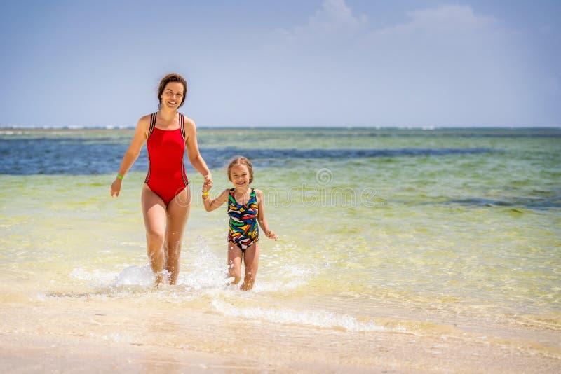 Junge Mutter und kleine Tochter, die den Strand in der Dominikanischen Republik genie?t stockfotografie
