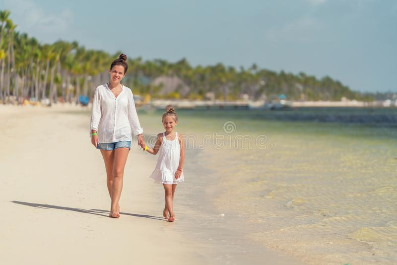 Junge Mutter und kleine Tochter, die den Strand in der Dominikanischen Republik genie?t lizenzfreies stockfoto