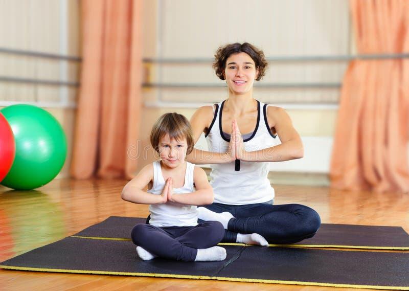Junge Mutter und kleine Tochter, die in der Turnhalle trainiert lizenzfreie stockfotografie