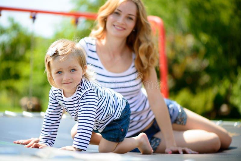 Junge Mutter und kleine Tochter, die am Spielplatz spielt lizenzfreies stockfoto