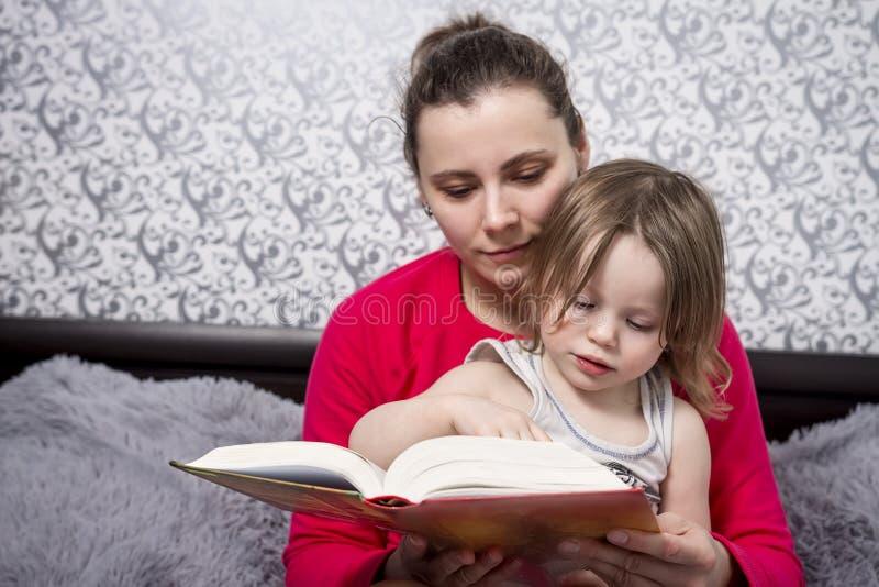Junge Mutter und kleine Tochter lasen Märchenbücher Aufbau mit Schrauben und Muttern Verbringen von Zeit mit Kindern Mutter und T stockbilder