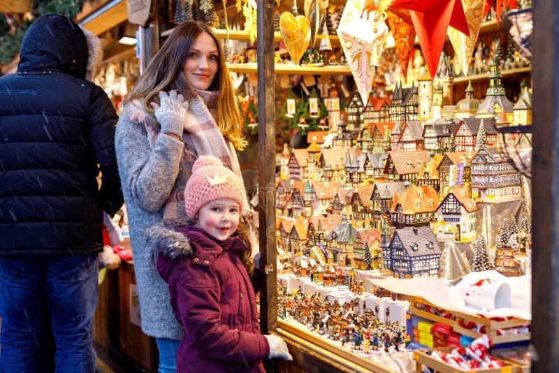 Junge Mutter und nette kleine Tochter, die Dekoration auf Weihnachtsmarkt vorwählt Schönheit und entzückendes Kindermädchen lizenzfreie stockfotos