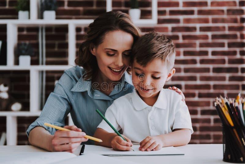 Junge Mutter und netter Sohn, die zusammen zu Hause zeichnet stockfotografie