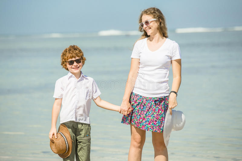 Junge Mutter und Sohn, die Spaß auf dem Strand hat lizenzfreie stockfotos