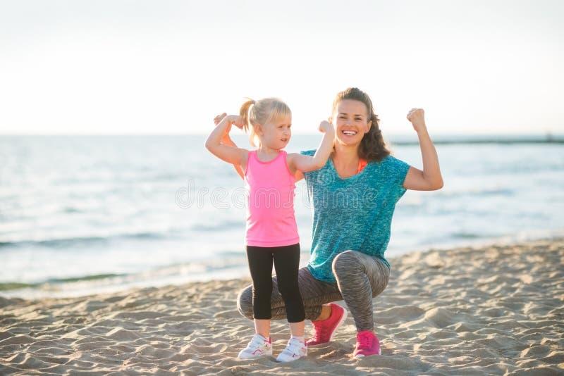 Junge Mutter und Tochter in der Eignung übersetzen auf dem Strand, der Arme biegt stockfoto