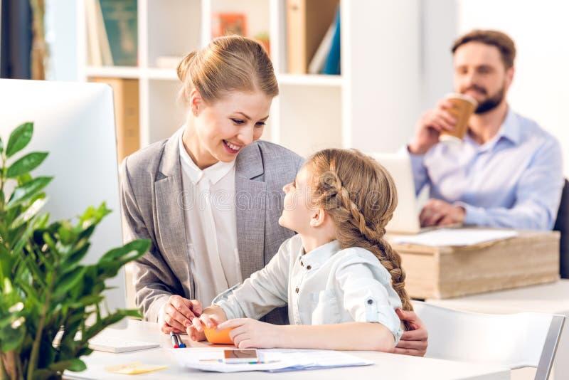 Junge Mutter und Tochter, die im Geschäftslokal spricht und umarmt stockbild