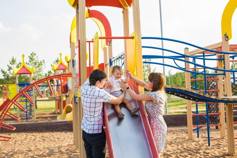 Junge Mutter und Vater, die mit ihrem Baby auf dem Spielplatz spielt lizenzfreie stockfotos