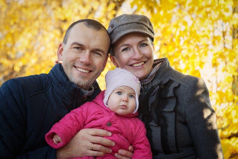 Junge Mutter und Vater und Baby haben Spaß im Herbst stockbild