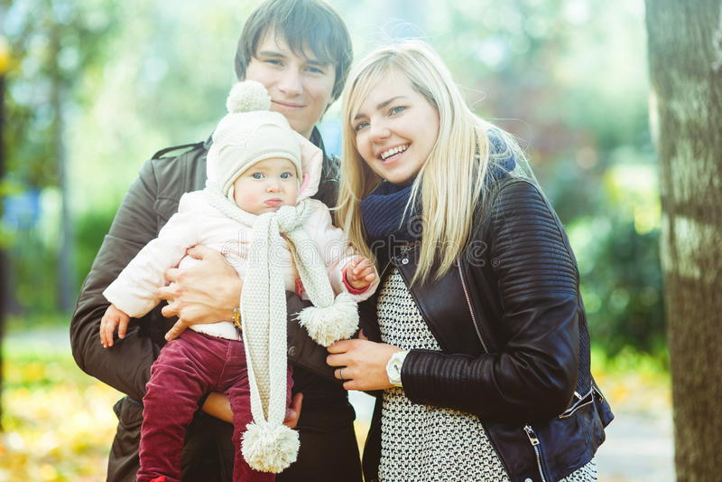 Junge Mutter und Vati mit Baby im Herbst parken stockfotografie