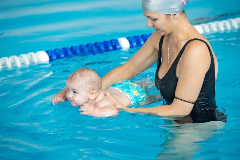 Junge Mutter unterrichten ihren kleinen Sohn, wie man in einem Schwimmen poo schwimmt lizenzfreie stockfotografie