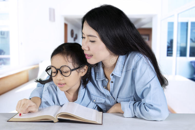 Junge Mutter unterrichtet ihr Kind zu lesen lizenzfreies stockfoto