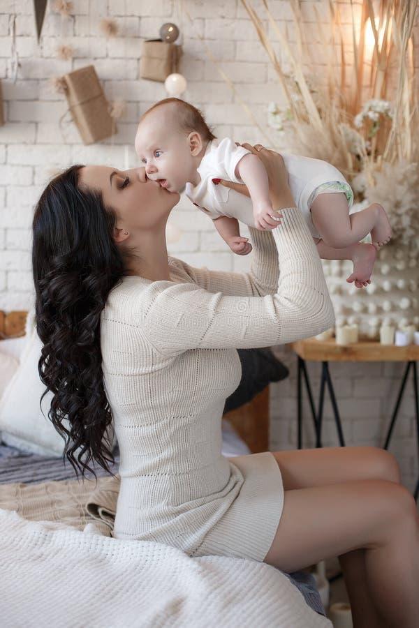Junge Mutter verbringt Zeit mit ihrem neugeborenen Sohn und zusammen spielt und liegt auf einem wei?en Bett im Schlafzimmer stockfoto