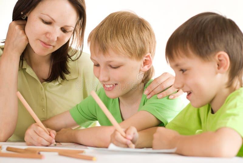 Junge Mutter zeichnet mit ihren Söhnen lizenzfreies stockbild