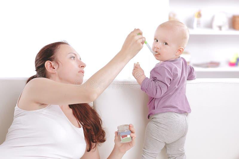 Junge Mutter zieht den Babyfruchtmus ein stockfotos