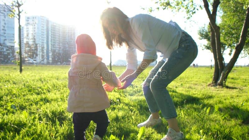 Junge Mutter zieht ihr Baby in ihren Armen und in Wegen im Park auf stockfotografie