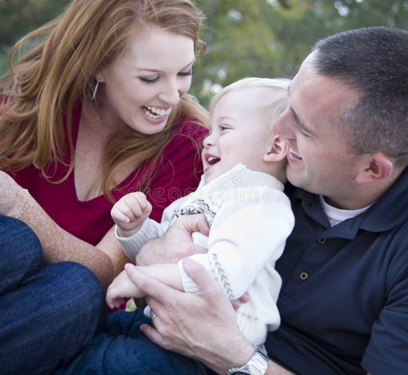 Junge Muttergesellschaft, die mit Kind-Jungen im Park lachen stockbilder