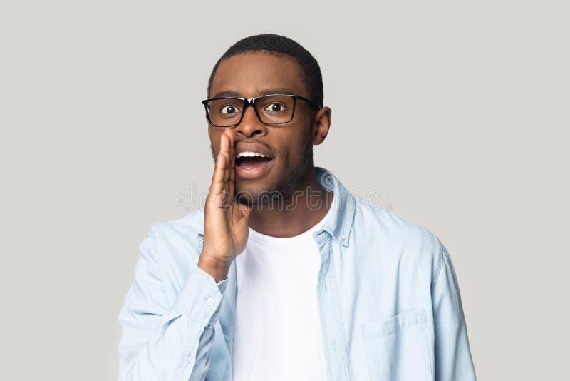 Junge mysteriöse afrikanische Amerikaner erzählen Geheimnis, flüstern Klatsch lizenzfreies stockfoto
