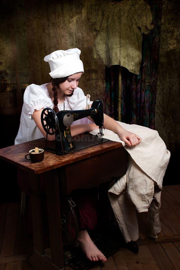 Junge Näherin mit alter Nähmaschine lizenzfreies stockfoto