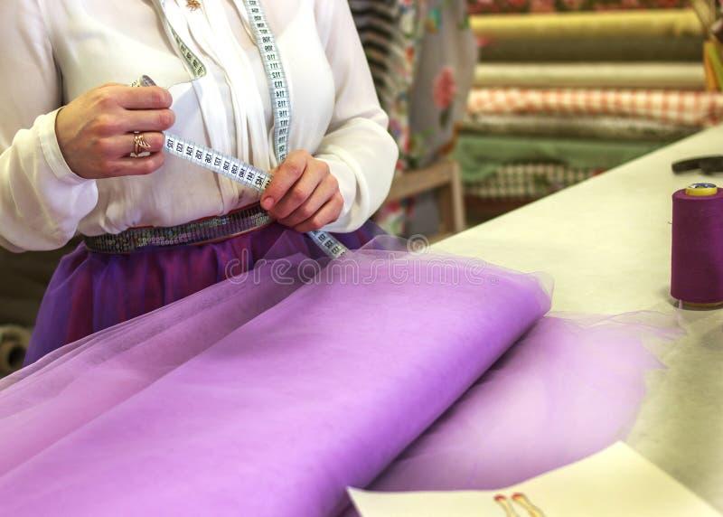 Junge Näherin stellt die Kleidung her, die Gewebe schneidet Schneider mit einer Nadel Die Näherin macht ein Maß lizenzfreies stockfoto