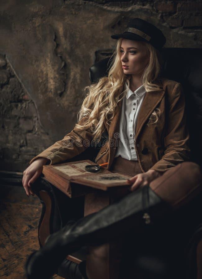 Junge nachdenkliche Frau im Bild von Sherlock Holmes sitzt im Lehnsessel und hält photoalbum in ihren Händen mit Vergrößerungsgla stockfotos