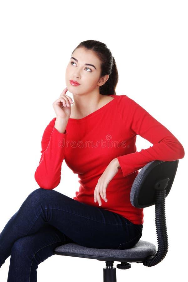 Junge nachdenkliche Studentenfrau, die auf Lehnsessel stationiert lizenzfreie stockfotos