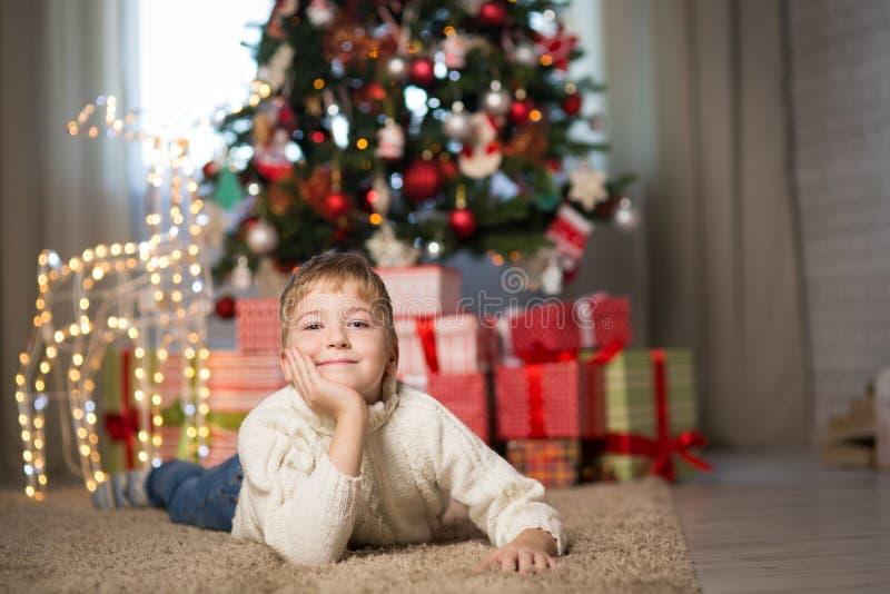 Junge nahe dem Weihnachtsbaum lizenzfreies stockbild