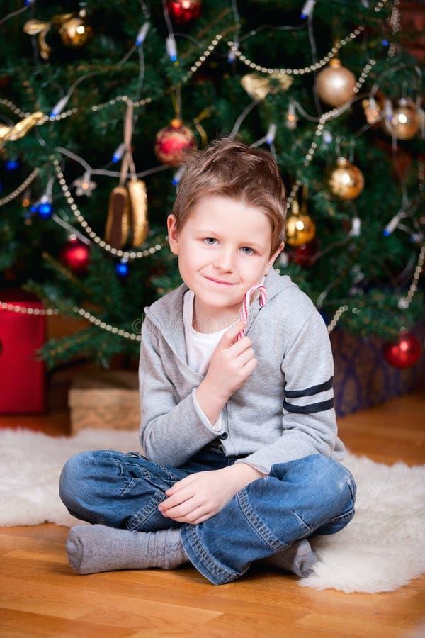 Junge nahe Weihnachtsbaum lizenzfreies stockfoto