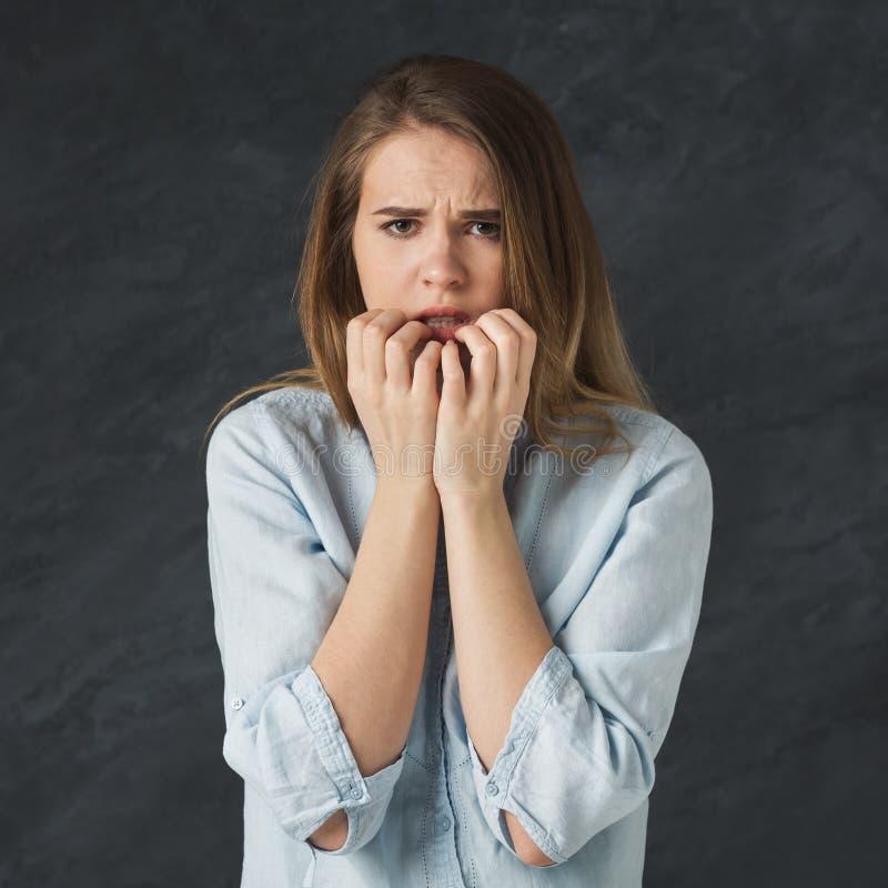 Junge nervöse Frau, die ihre Nägel beißt stockfoto