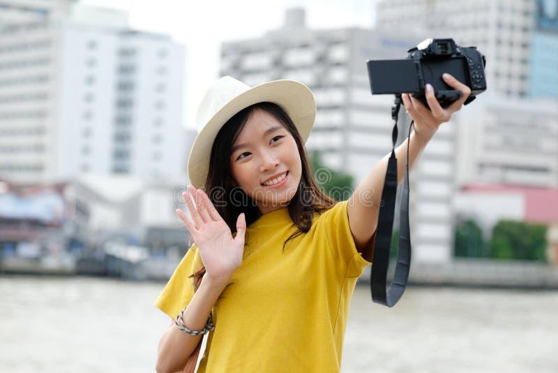 Junge nette asiatische Frau in der zufälligen Art unter Verwendung der Kamera zum selfie im städtischen Stadtfreienhintergrund, F lizenzfreie stockfotos