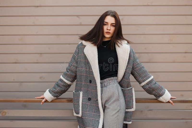 Junge nette brunette Frau in einer modischen Plaidjacke in einem schwarzen T-Shirt in den stilvollen grauen Hosen steht Stellung  lizenzfreie stockfotografie