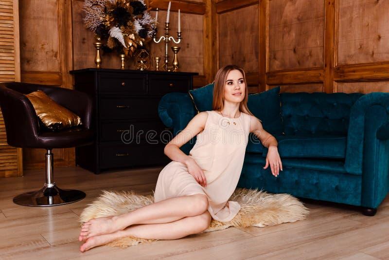 Junge nette durchdachte Frau in einem hellen beige Kleid, das auf einer flaumigen Wolldecke nahe dem grünen Sofa sitzt lizenzfreie stockbilder
