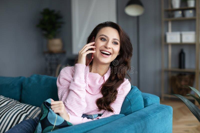 Junge nette Frau, die am Handy sitzt auf bequemem Sofa spricht lizenzfreies stockfoto