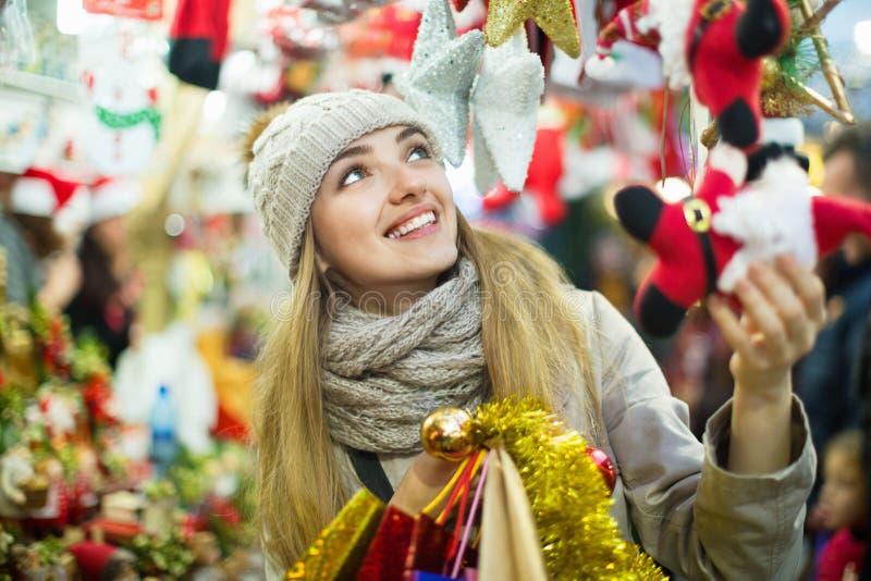 Junge nette glückliche Frau, die Weihnachtsdekoration wählt stockfotos