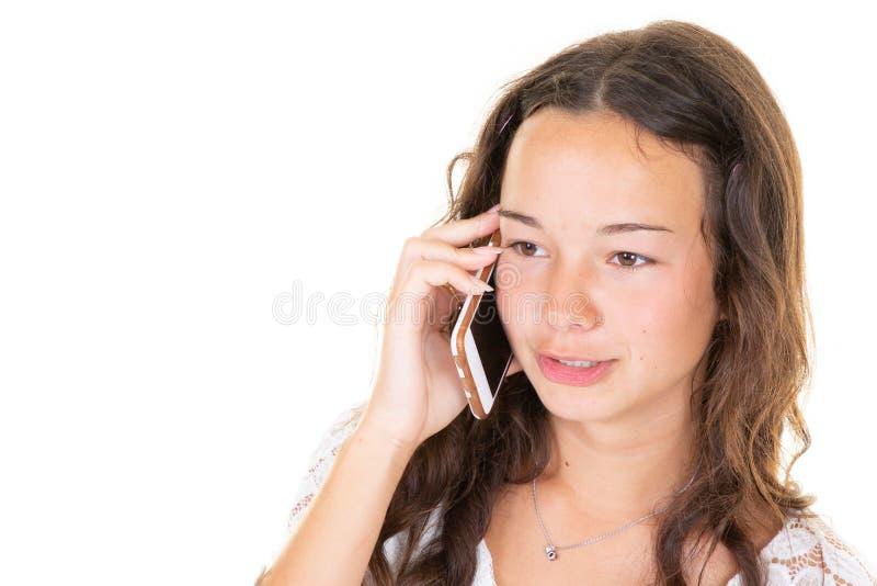 Junge nette Jugendliche, die am Telefon über weißem Hintergrund spricht stockfotografie