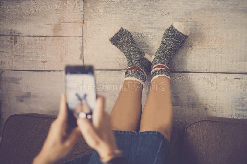 Junge nette kaukasische Dame auf dem Sofa, das Foto mit Smartphone an ihren Füßen mit den glücklichen und lustigen Socken macht A lizenzfreies stockbild